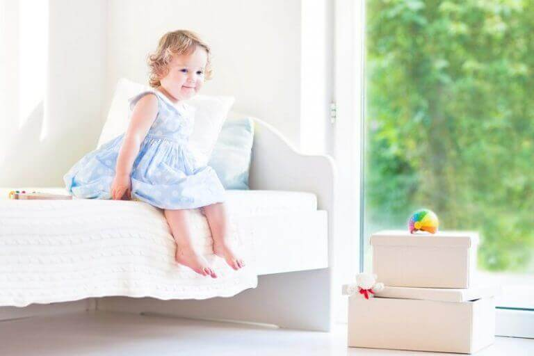 toddler sitting on a comfortable bed